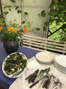 Orangea blommor i vas. Grönsallad samt tallrikar och bestick